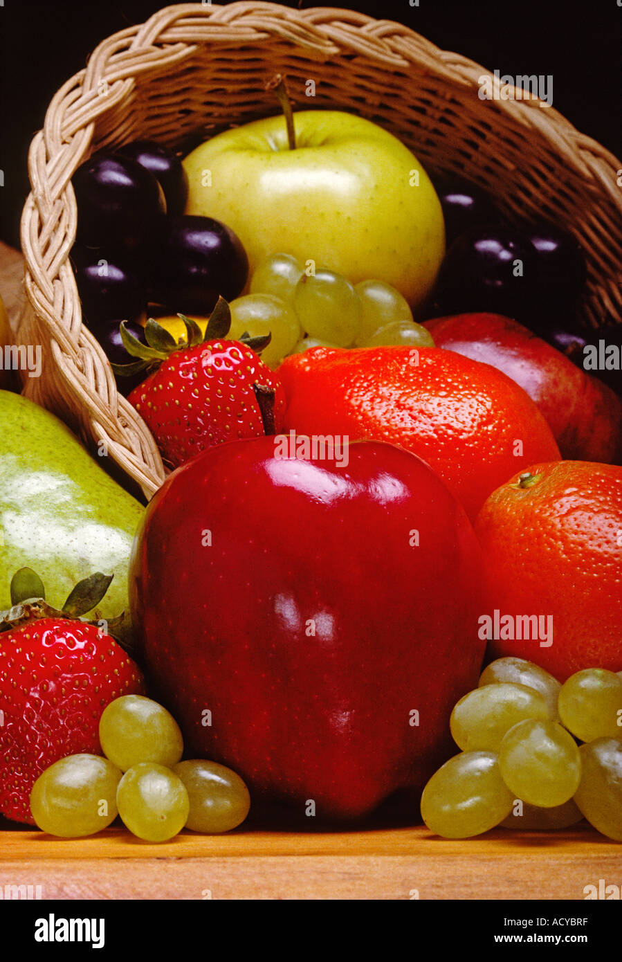 CORNUCOPIA of fruit with apples tangelos grapes strawberries and pear - Stock Image