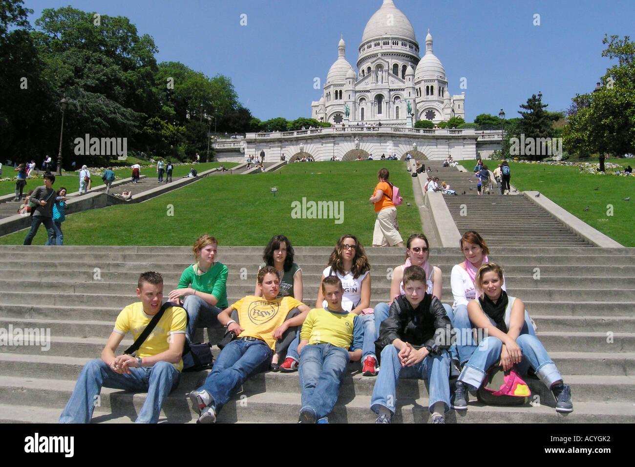 School group of Caucasian teenagers posing for camera in front of Sacre Coeur Paris - Stock Image