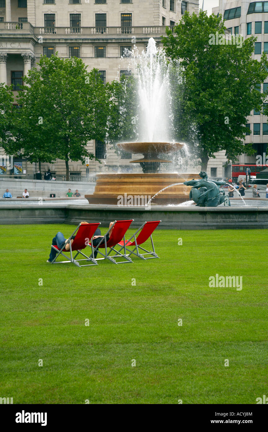 "Red deck-chairs on green turfed Trafalgar Square as part of ""Village London"" event May 2007 Stock Photo"