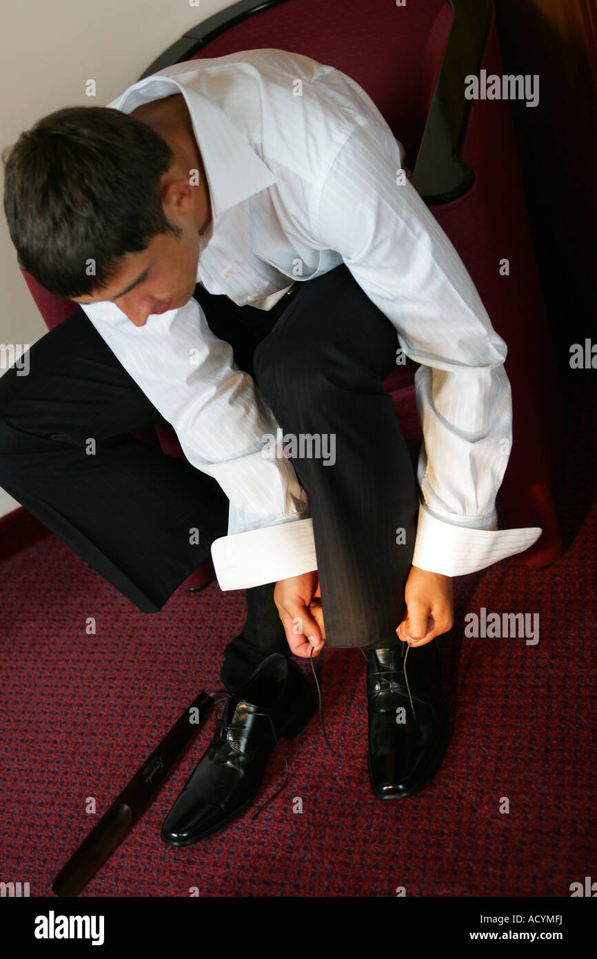 A portrait of a goom on his wedding day pictured tying up his shoe laces as he gets dressed. - Stock Image