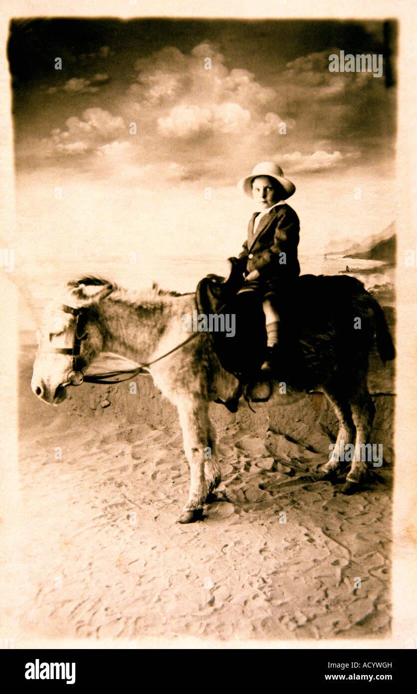 Old fading snapshot of child on seaside donkey - Stock Image