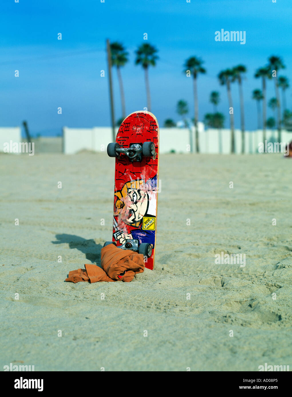 skate board and towel standing upright in the the snad, at venice beach  u.s. - Stock Image
