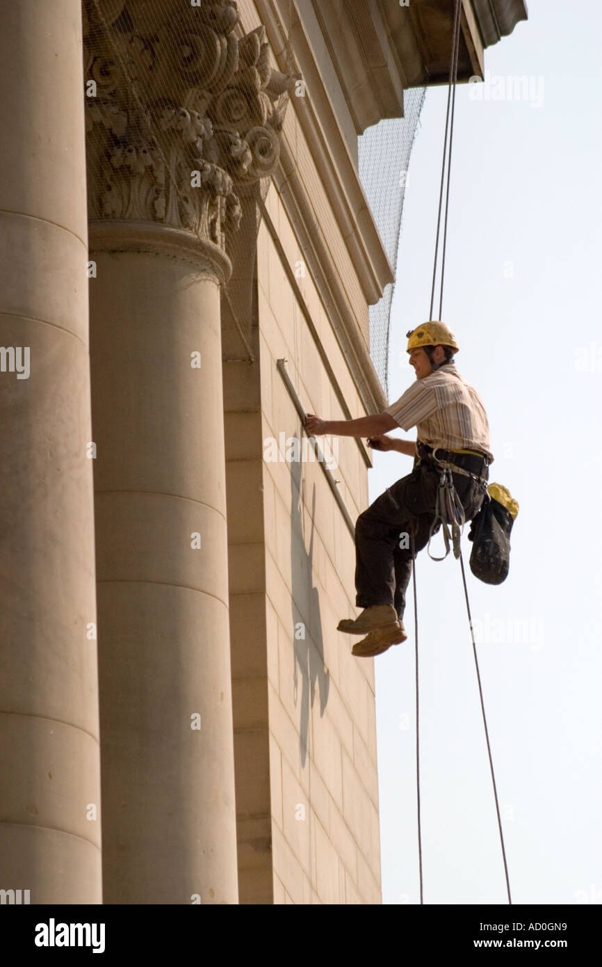 Worker abseiling down the front of Sheffield City Hall to fix banner to facade - Stock Image