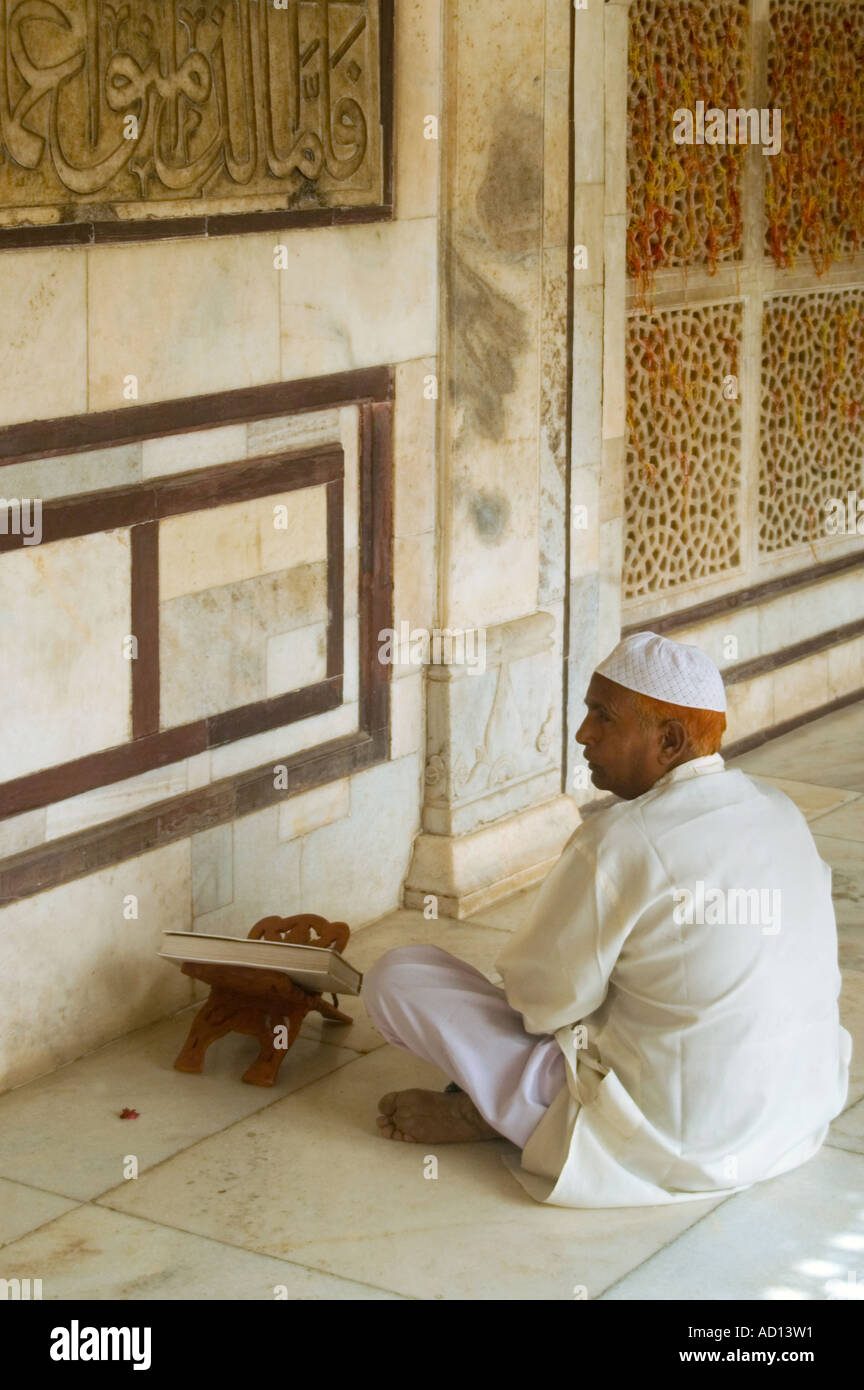 Vertical close up of an Indian man sitting at an inscription on a wall reading from a prayer book inside Salim Chisti's tomb. - Stock Image