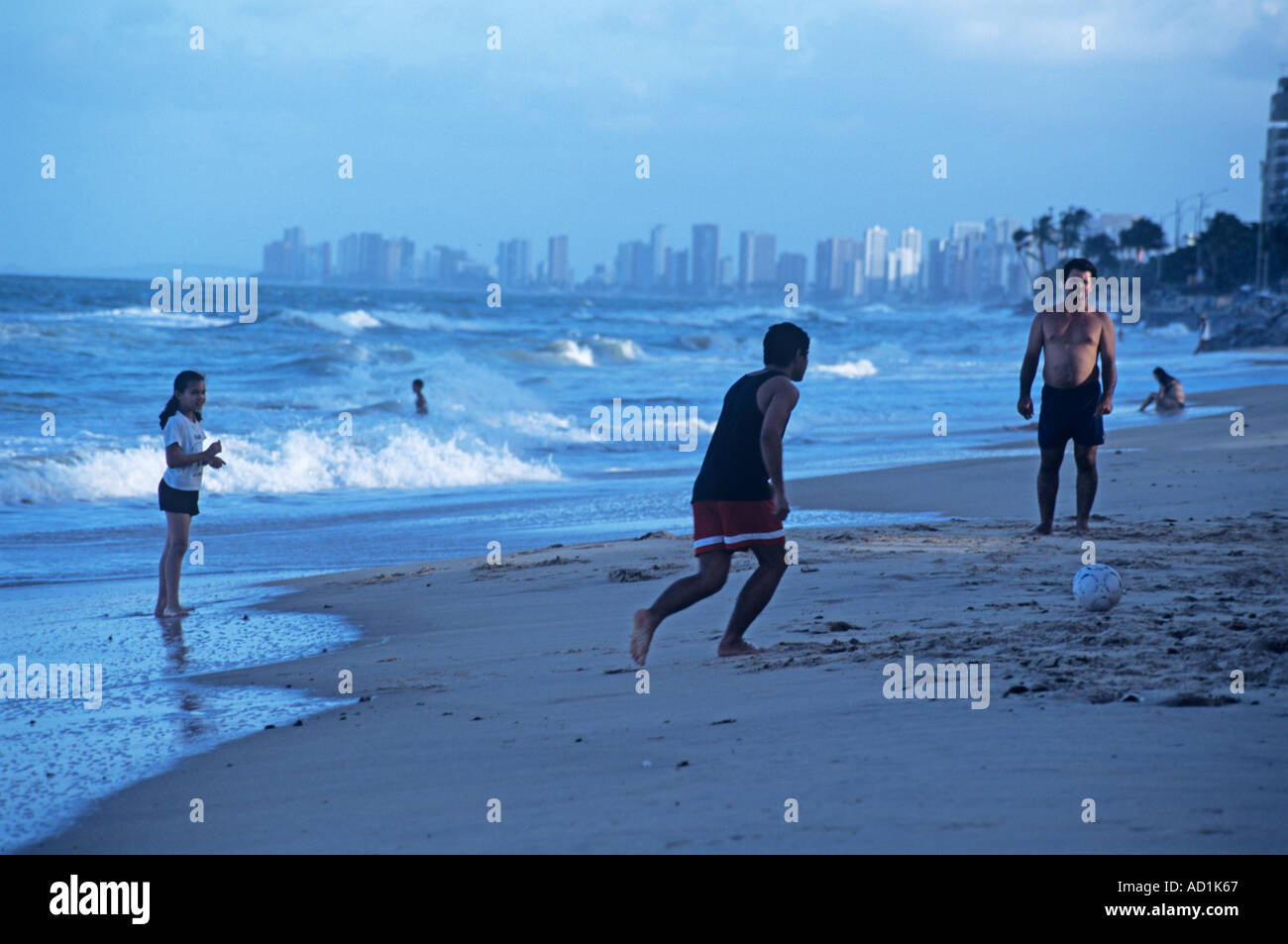 Beachgoers play football on Recife's 7 km long Praia de Boa Viagem even as dusk falls - Stock Image