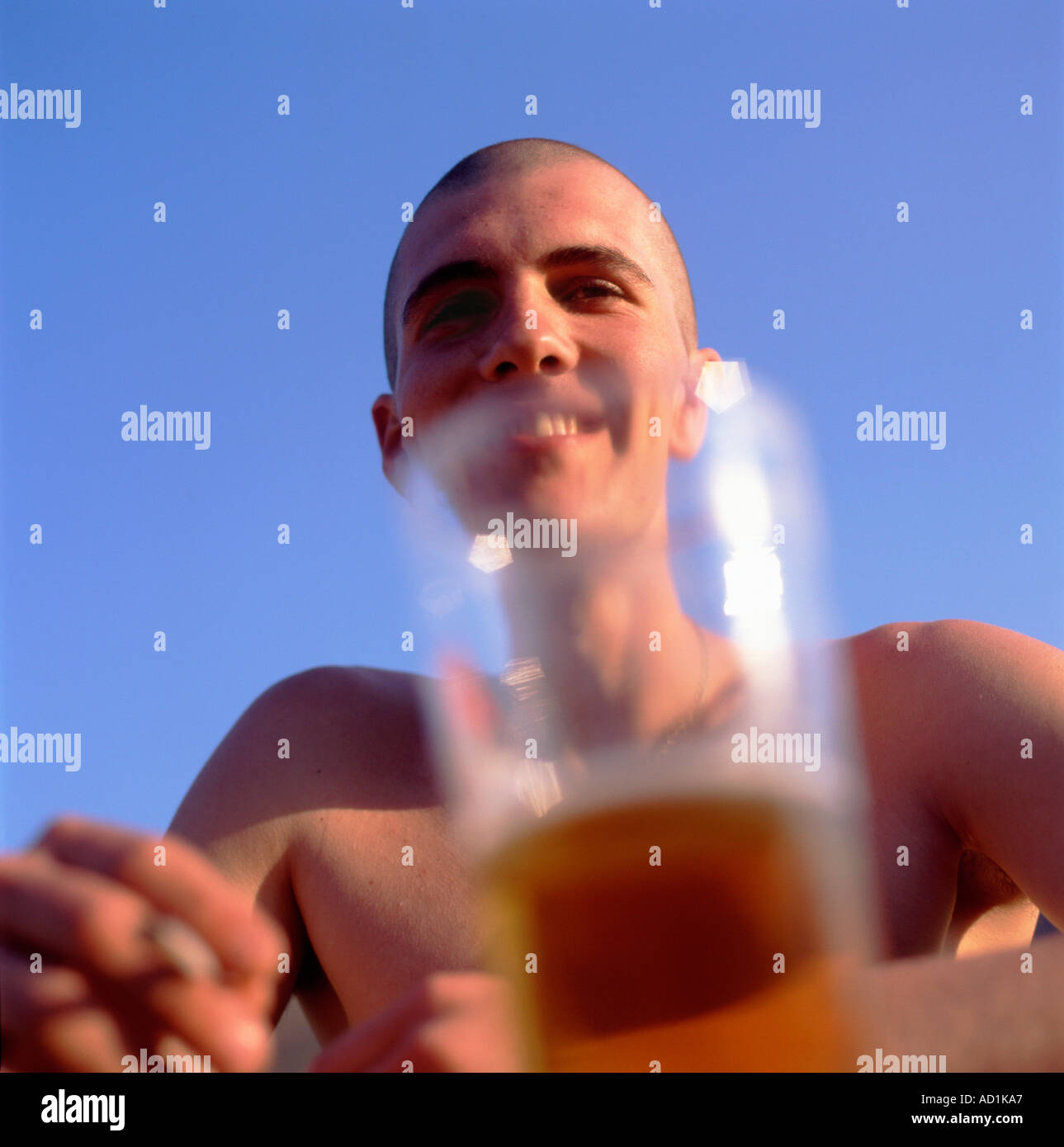 Young man smiling drinking a pint of beer glass on a summer day in Wales  UK   KATHY DEWITT - Stock Image