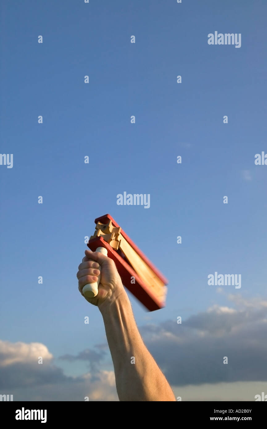 Hand waving a traditional football rattle in the air - Stock Image