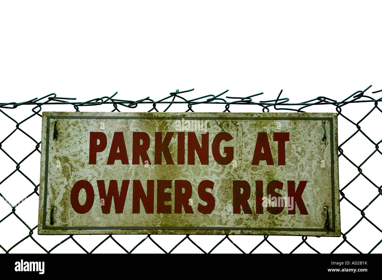 Grungey old Parking sign on a wire fence isolated on white - Stock Image