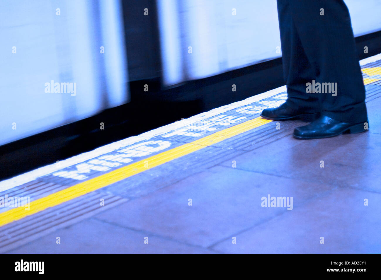 Young businessman stands on London Underground platform as tube train enters station - Stock Image