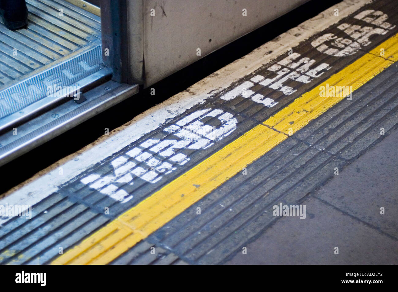 Open tube train door on London Underground platform with mind the gap sign on platform floor - Stock Image