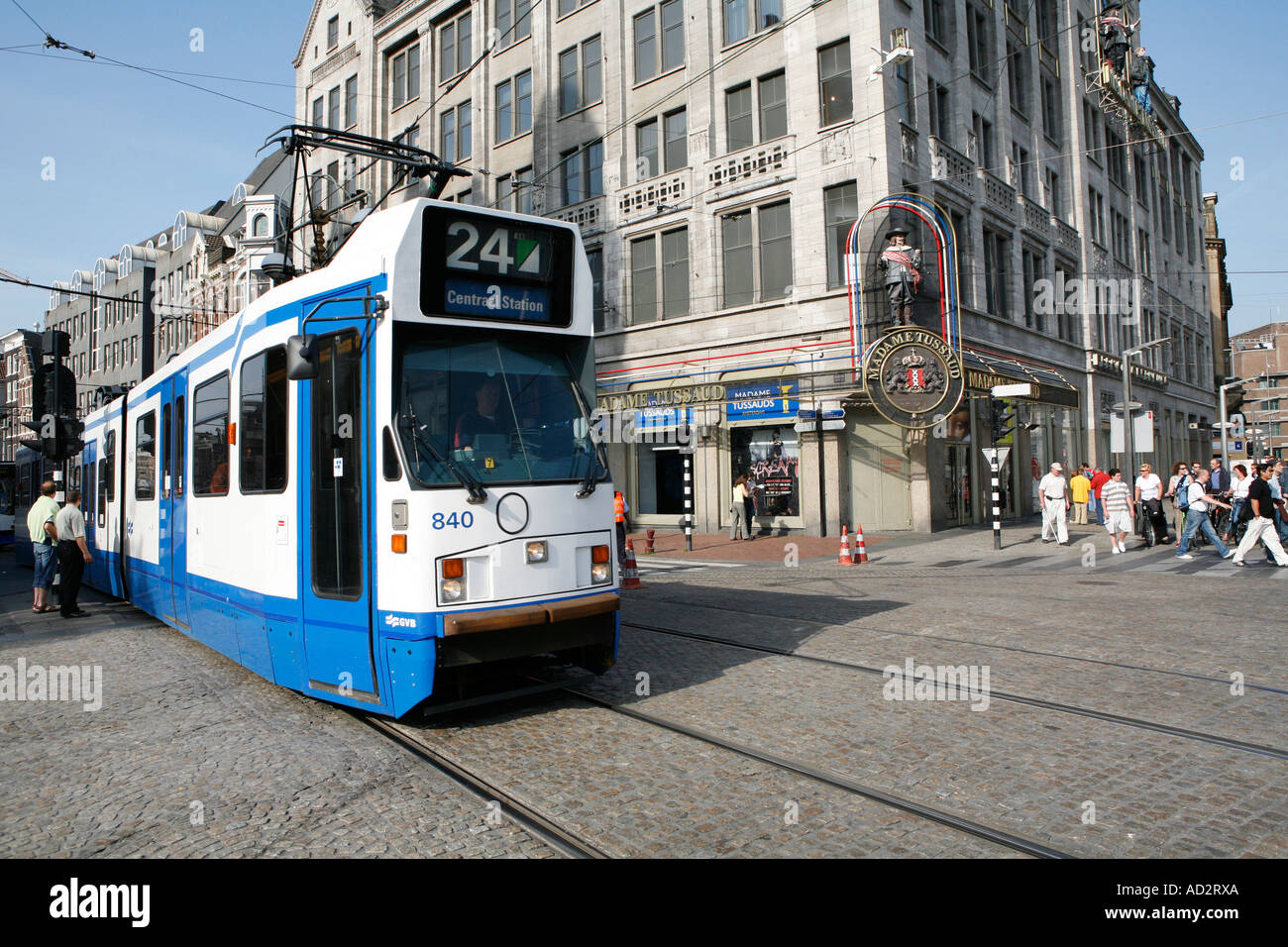 Madame Tussaud museum on Dam Square in Amsterdam, and a typical Dutch tram. - Stock Image