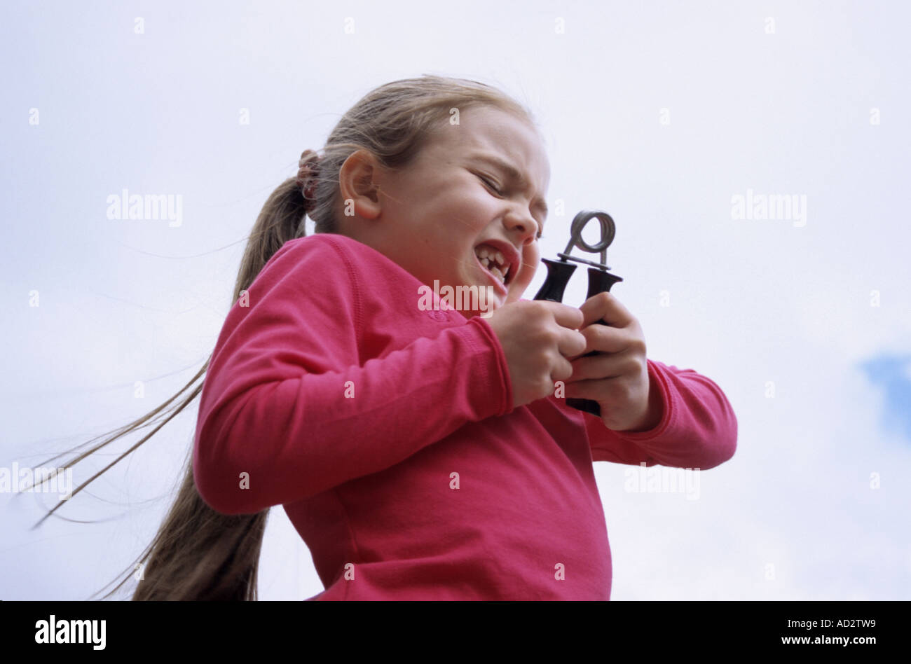 Young Girl Getting To Grips With Hand Strengthener - Stock Image