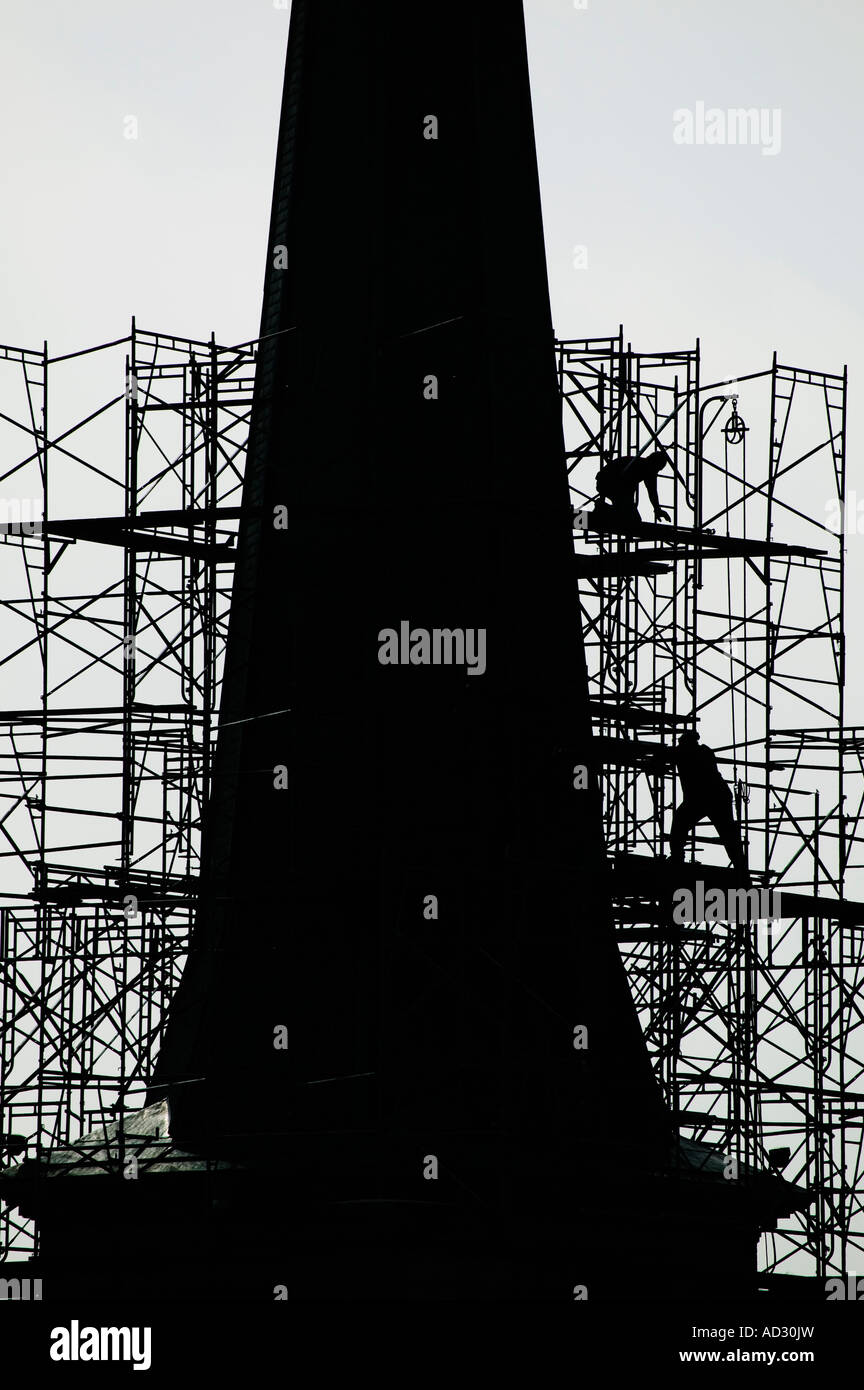 Laborers in silhouette work on scaffolding around a church steeple in Amsterdam New York - Stock Image