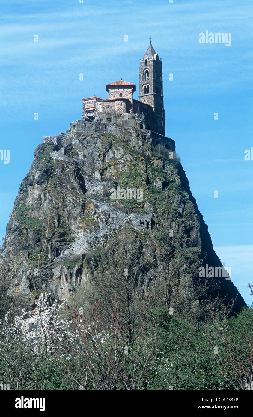The pilgrimage chapel of St.Michel d'Aiguilhe on top of a volcanic rock pinnacle is a dramatic sight in France's - Stock Image