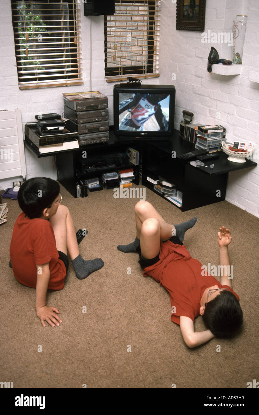 Two brothers lounging in front of the television - Stock Image