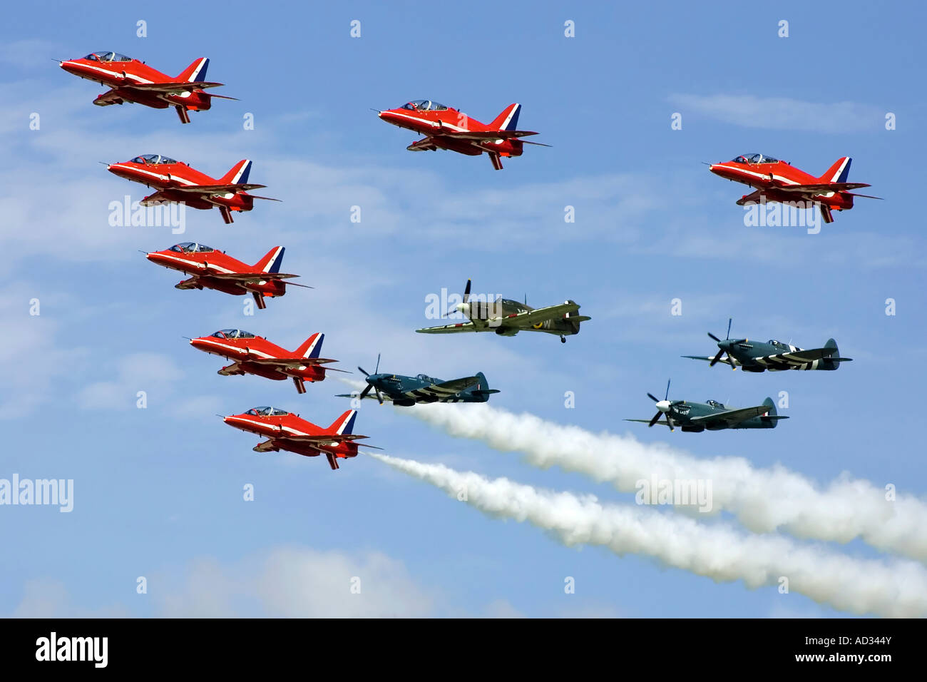The RAF Red Arrows formation aerobatic team flying in formation with a WW2 RAF Hurricane and 3 RAF Spitfire fighters - Stock Image