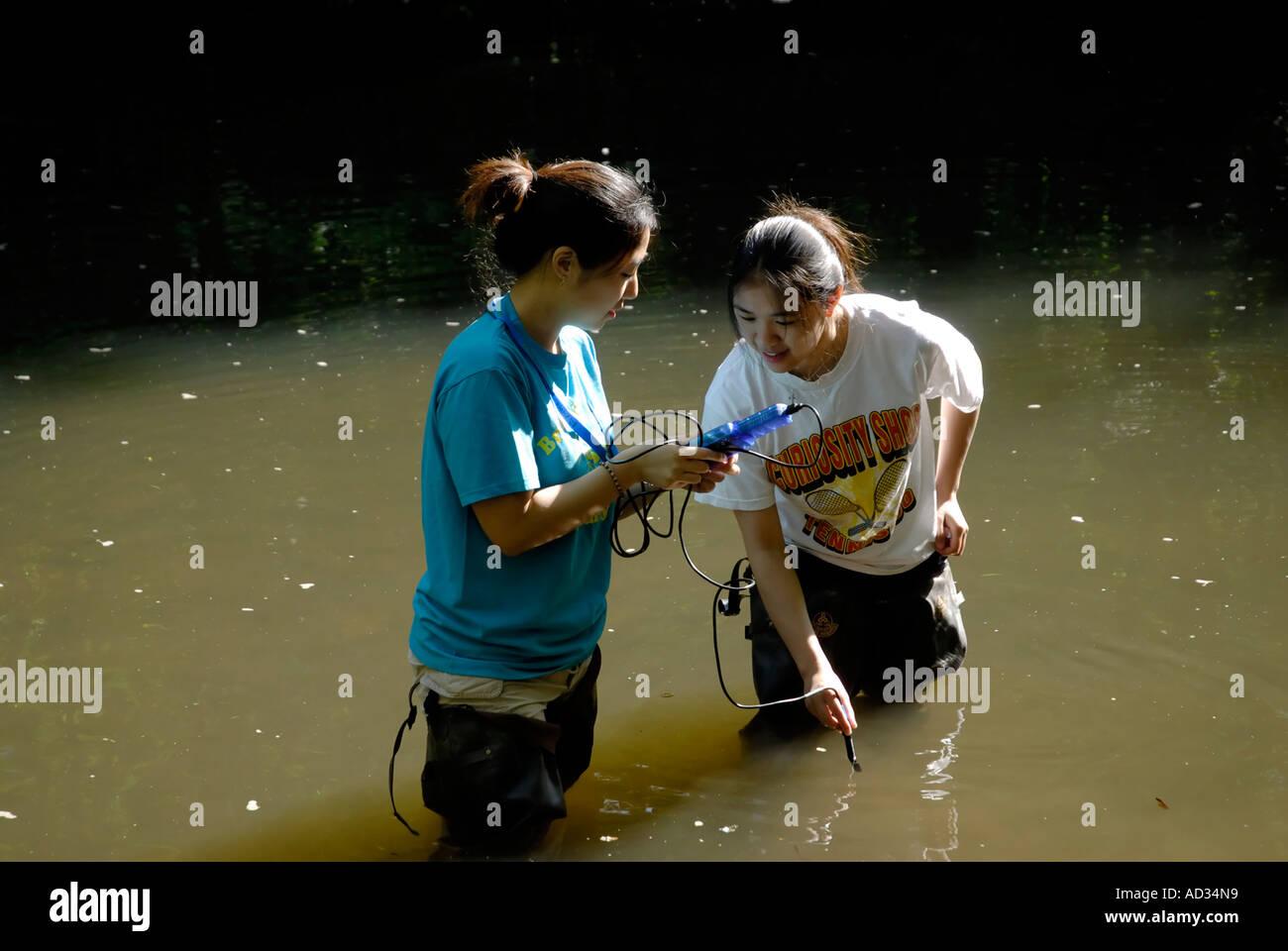 Teenage Asian-American girls sampling river water with digital Stock