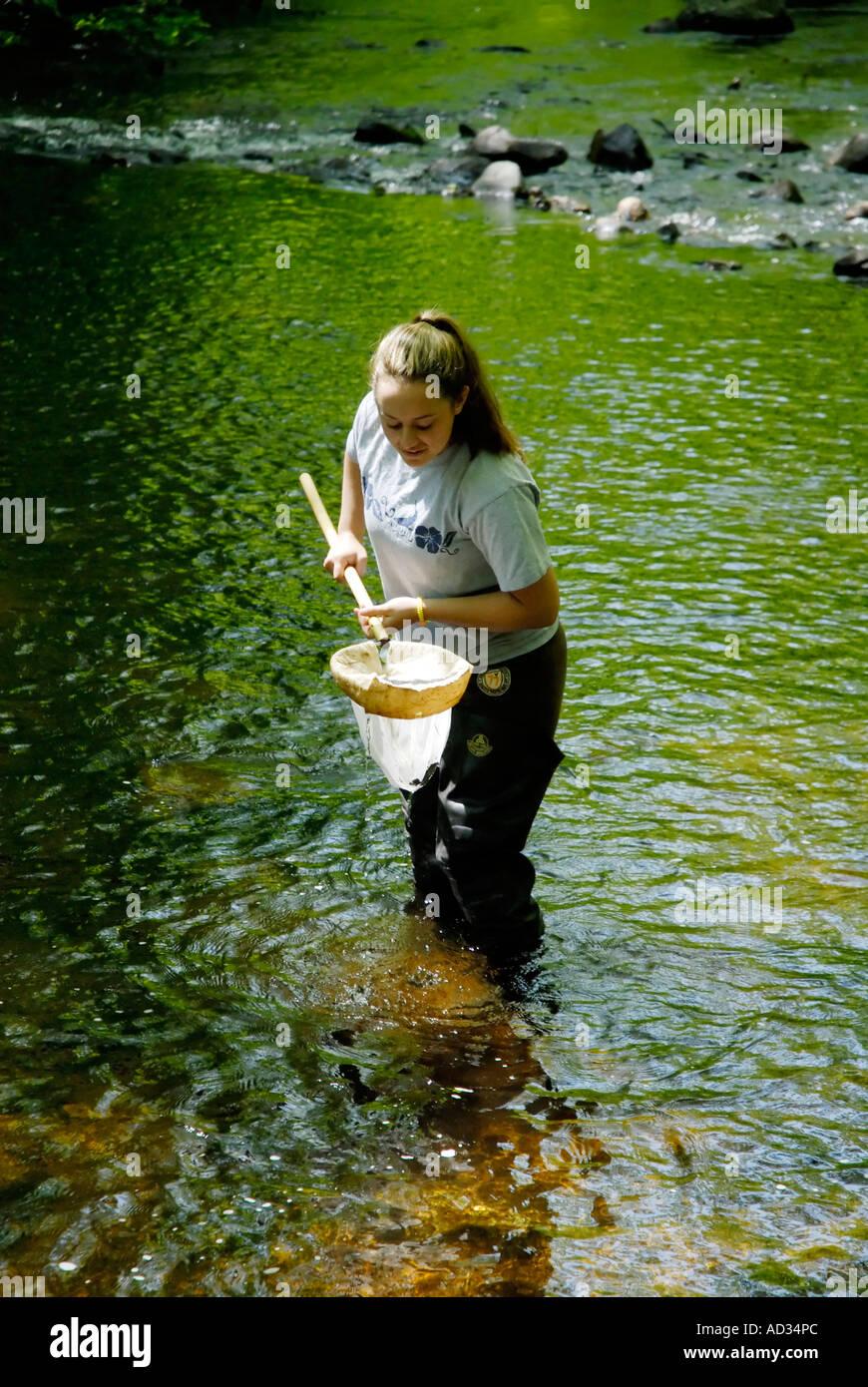 Teenage girl using net sampling river water for fish and