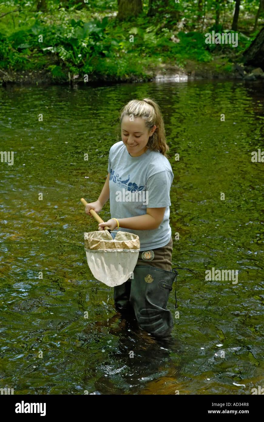 Teenage girl using net sampling river water for fish and invertebrate biological indicators of water quality Stock Photo