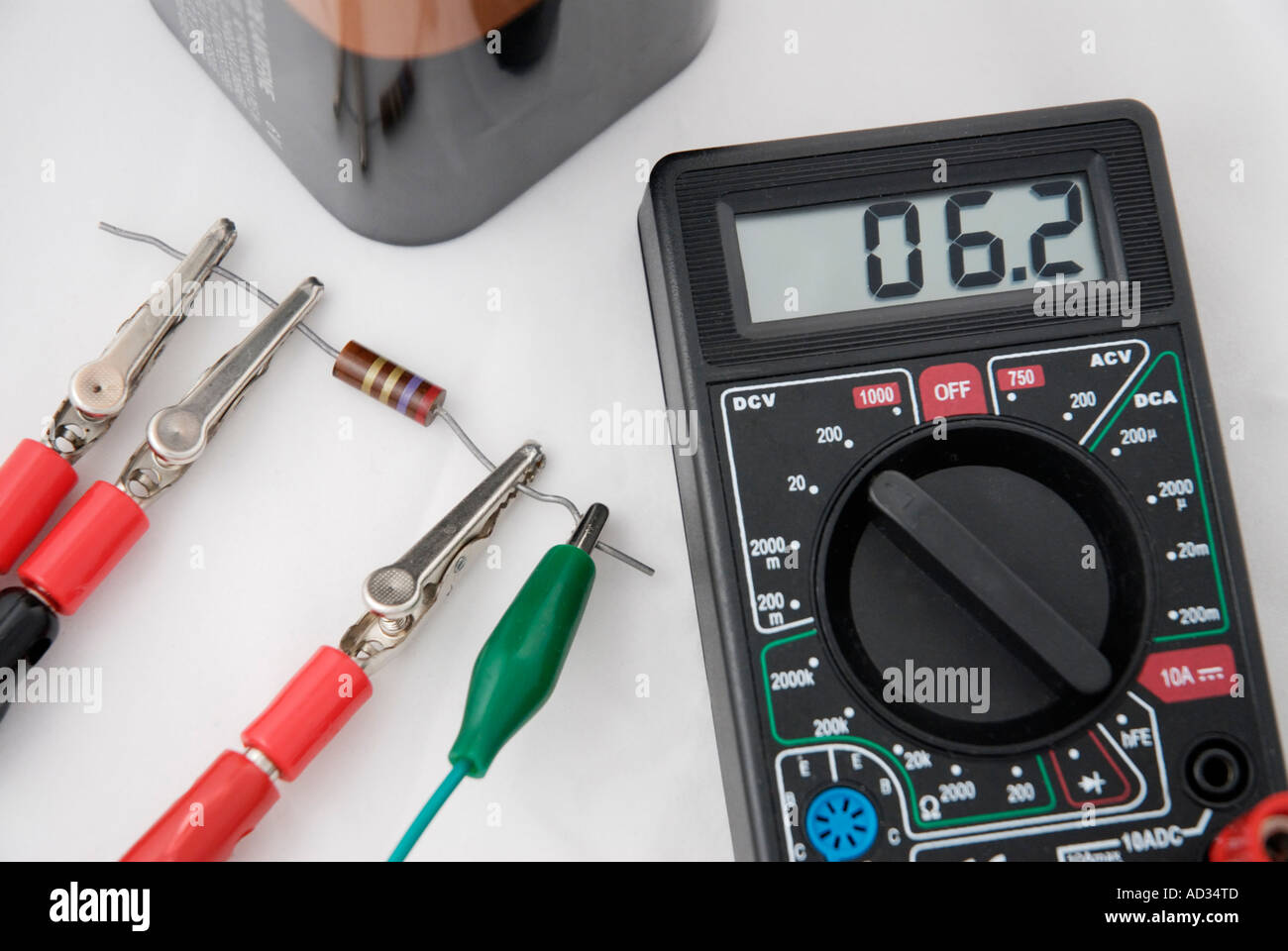 Digital multimeter connected to circuit including battery and resistor - Stock Image