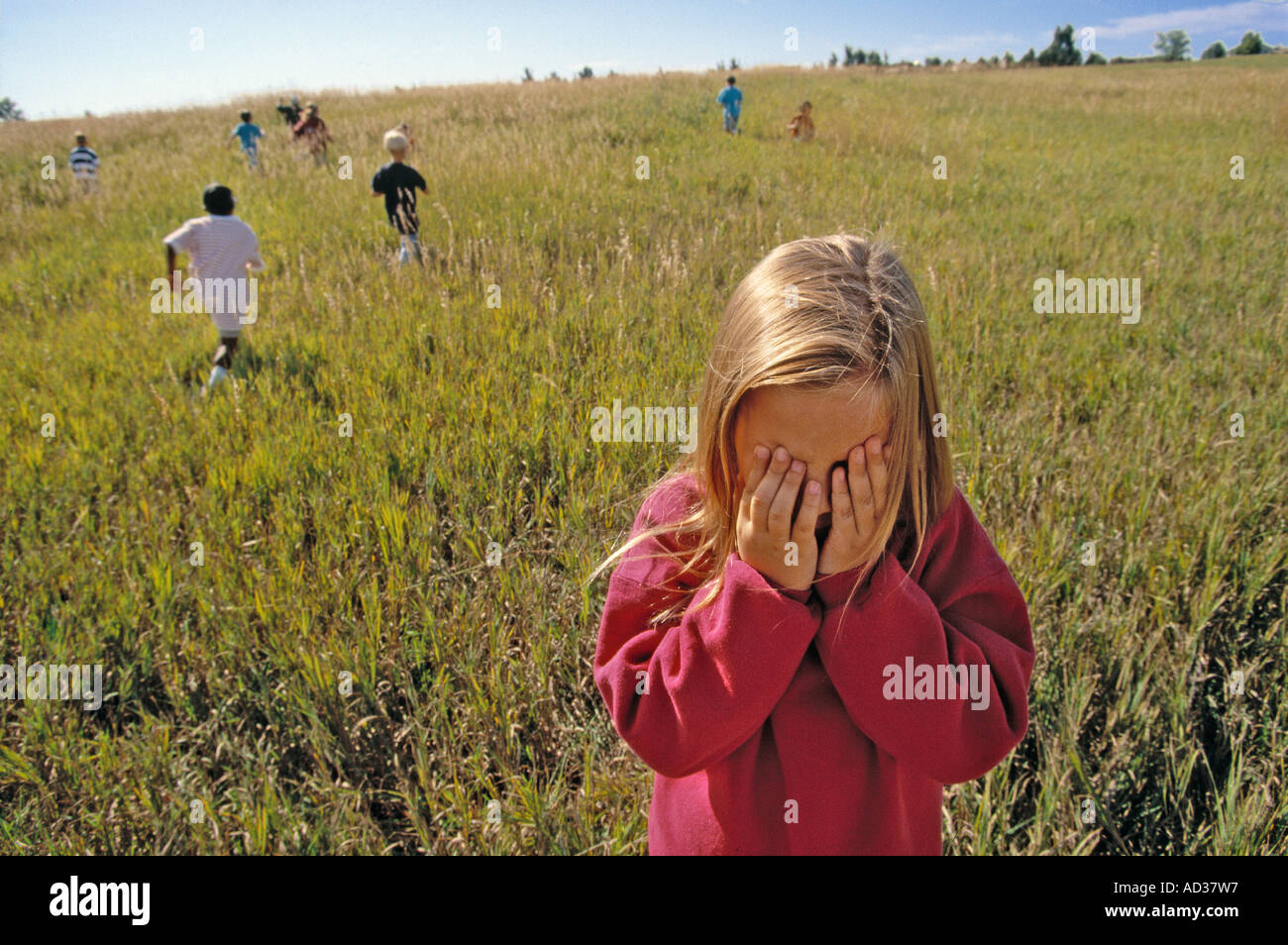 Blond haired girl playing hide and seek with other children in sunlit field. - Stock Image