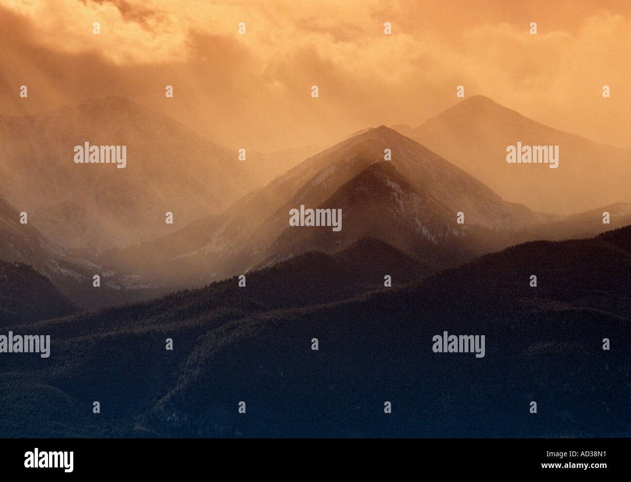 Mountain peaks with mist and clouds at sunset. - Stock Image