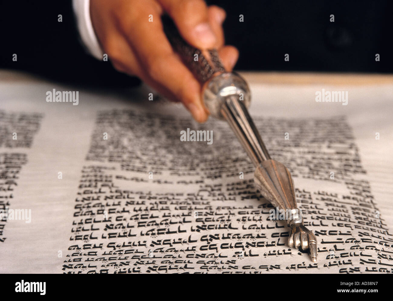 Jewish Rabbi uses silver hand pointer to read a Torah. - Stock Image