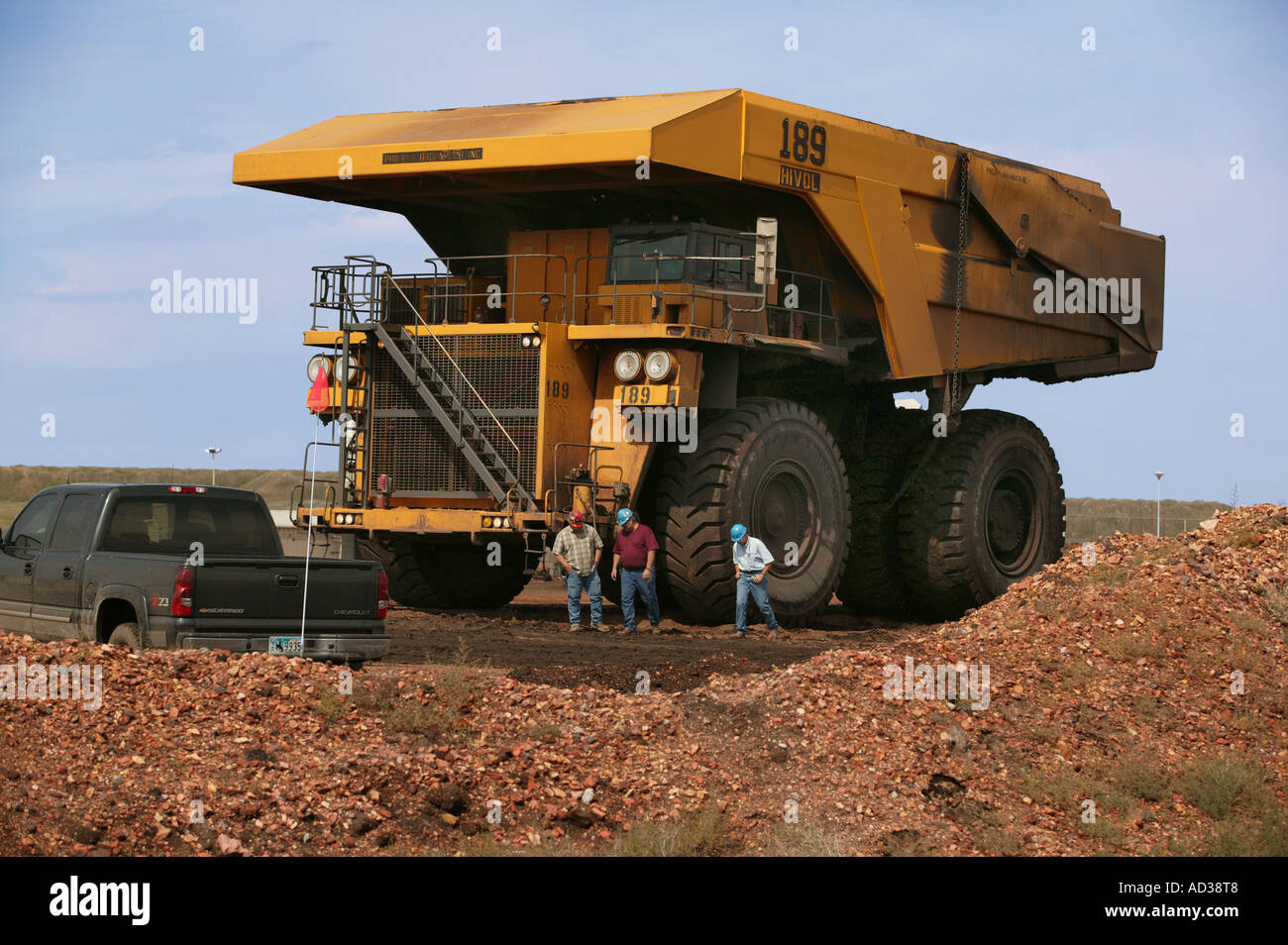 Massive dump truck with people and pickup truck in front at the black thunder coal mine near gillette wyoming usa