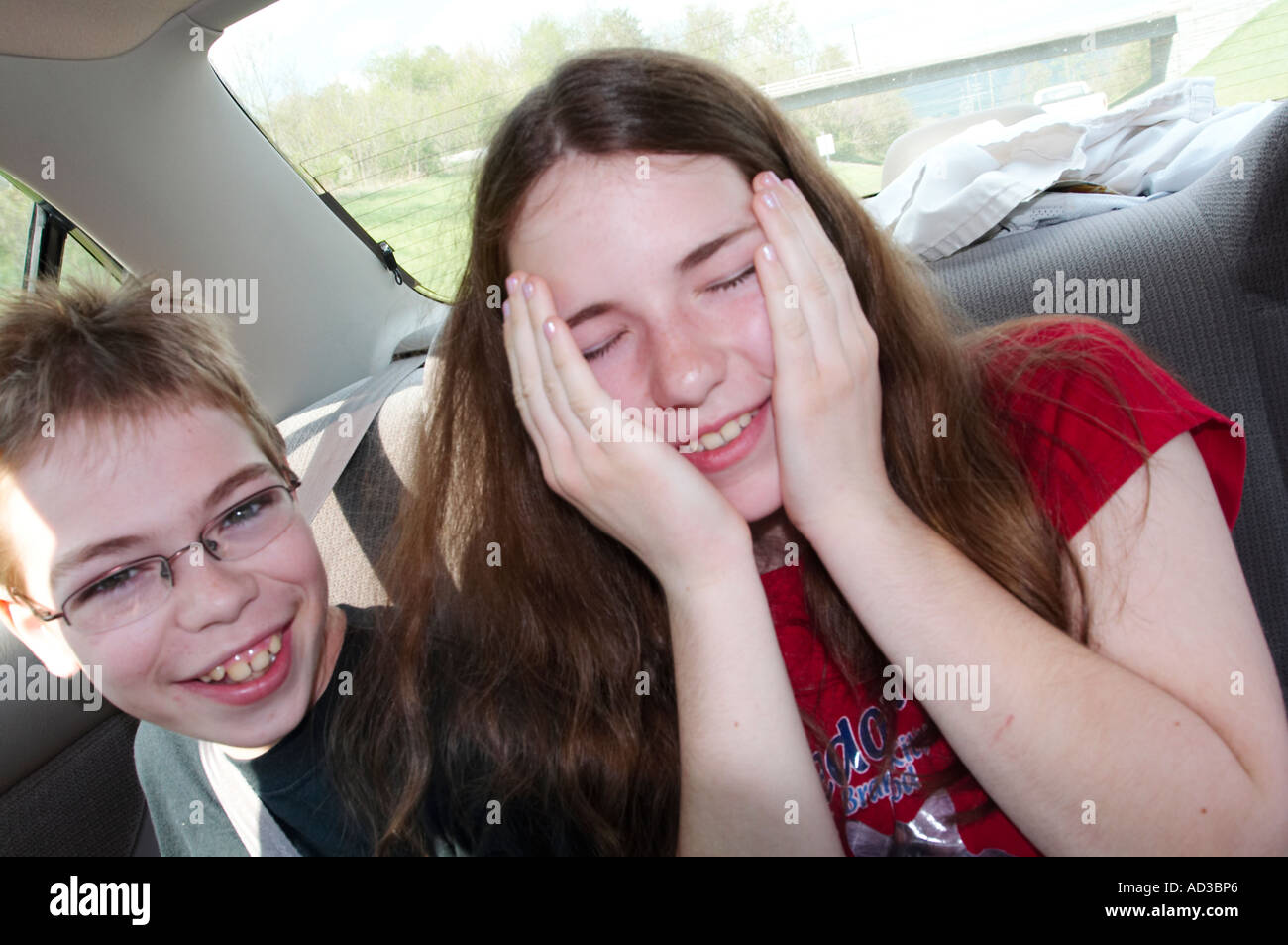 A brother and sister making funny faces in the back seat of a car, automobile. Stock Photo