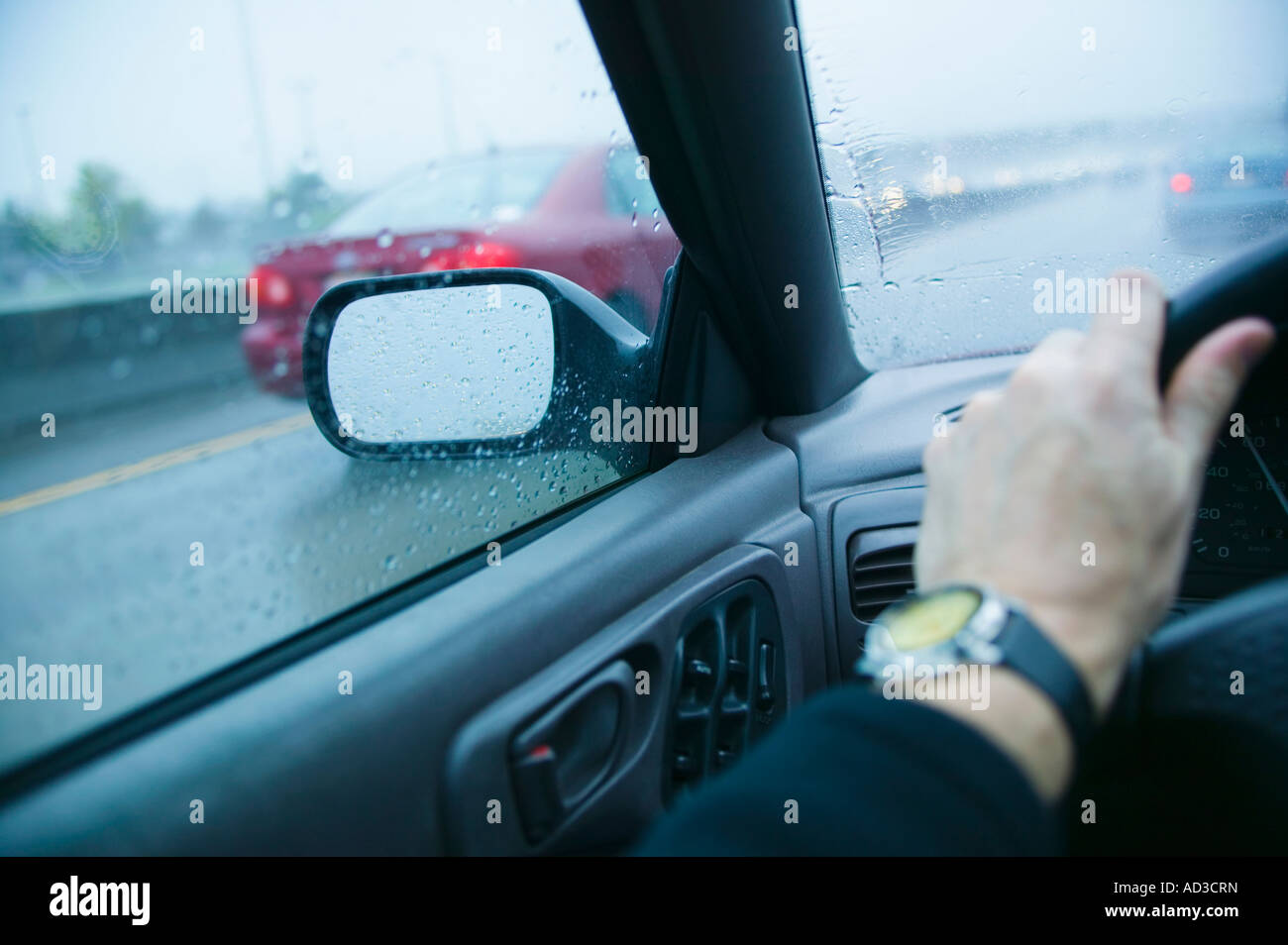 Drivers arm and view through windows on a highway in the rain - Stock Image