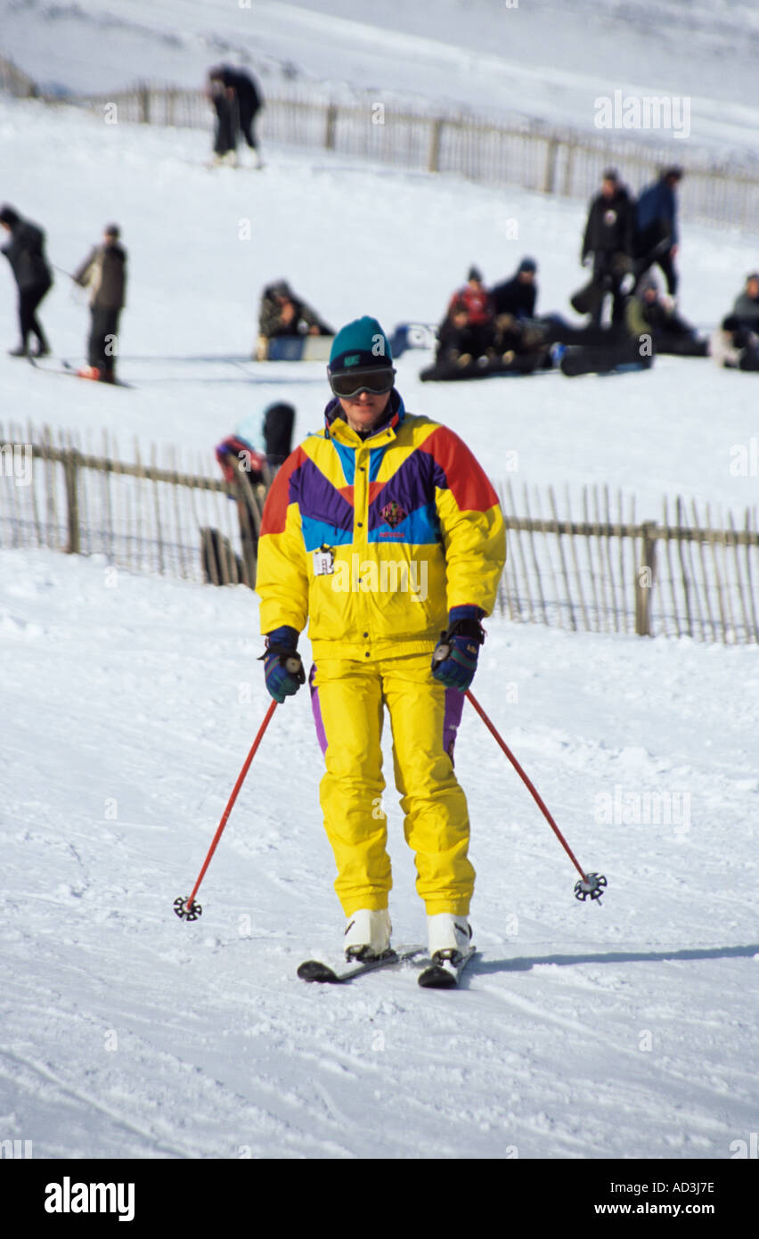 MORAY SCOTLAND UK February Man in a bright yellow ski suit skiing down on of the slopes at the Lecht Ski Centre - Stock Image