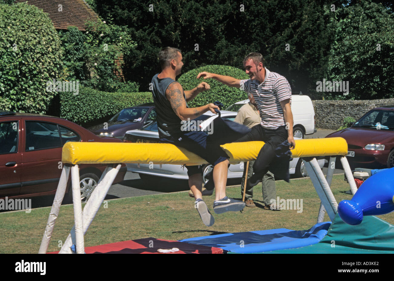 TILFORD SURREY UK July Two men trying to knock the other off a greasy pole at the annual summer fete - Stock Image