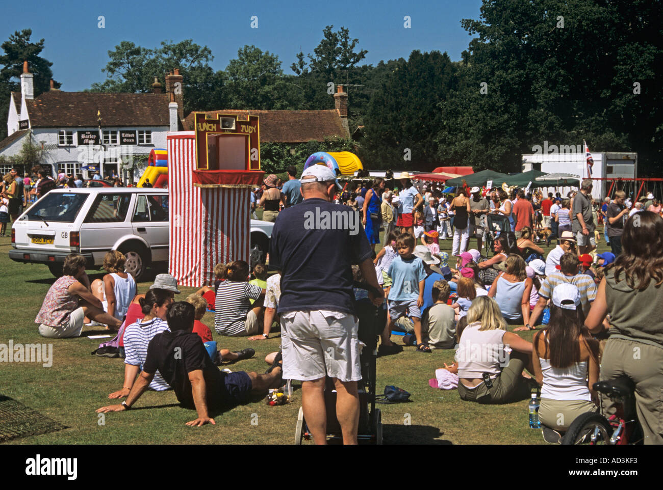 TILFORD SURREY UK July Children are enthralled by the antics of Punch and Judy at the annual summer fete - Stock Image