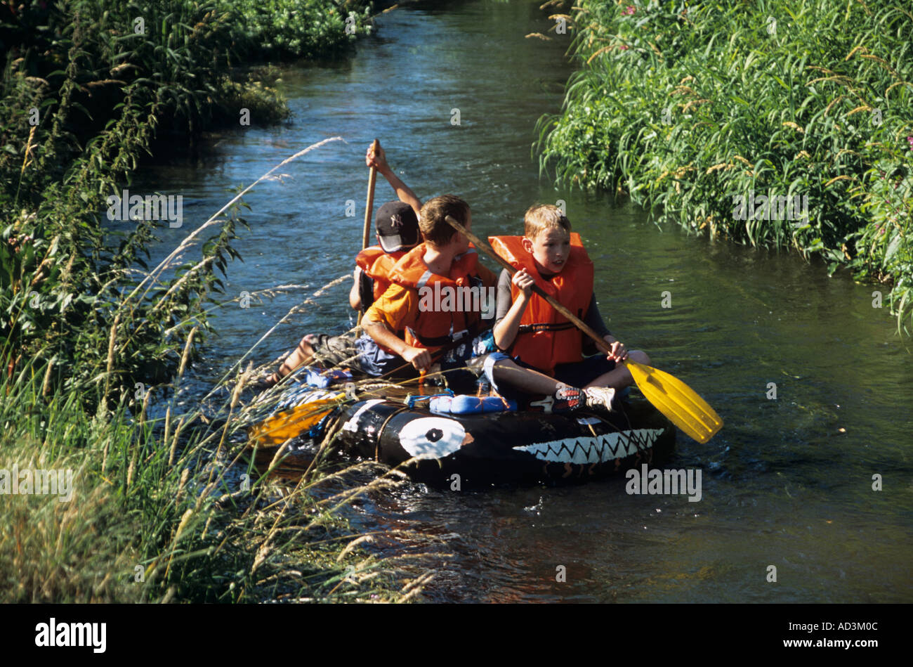 TILFORD SURREY England UK July Some of the raft race contestants paddling their raft down the River Wey - Stock Image