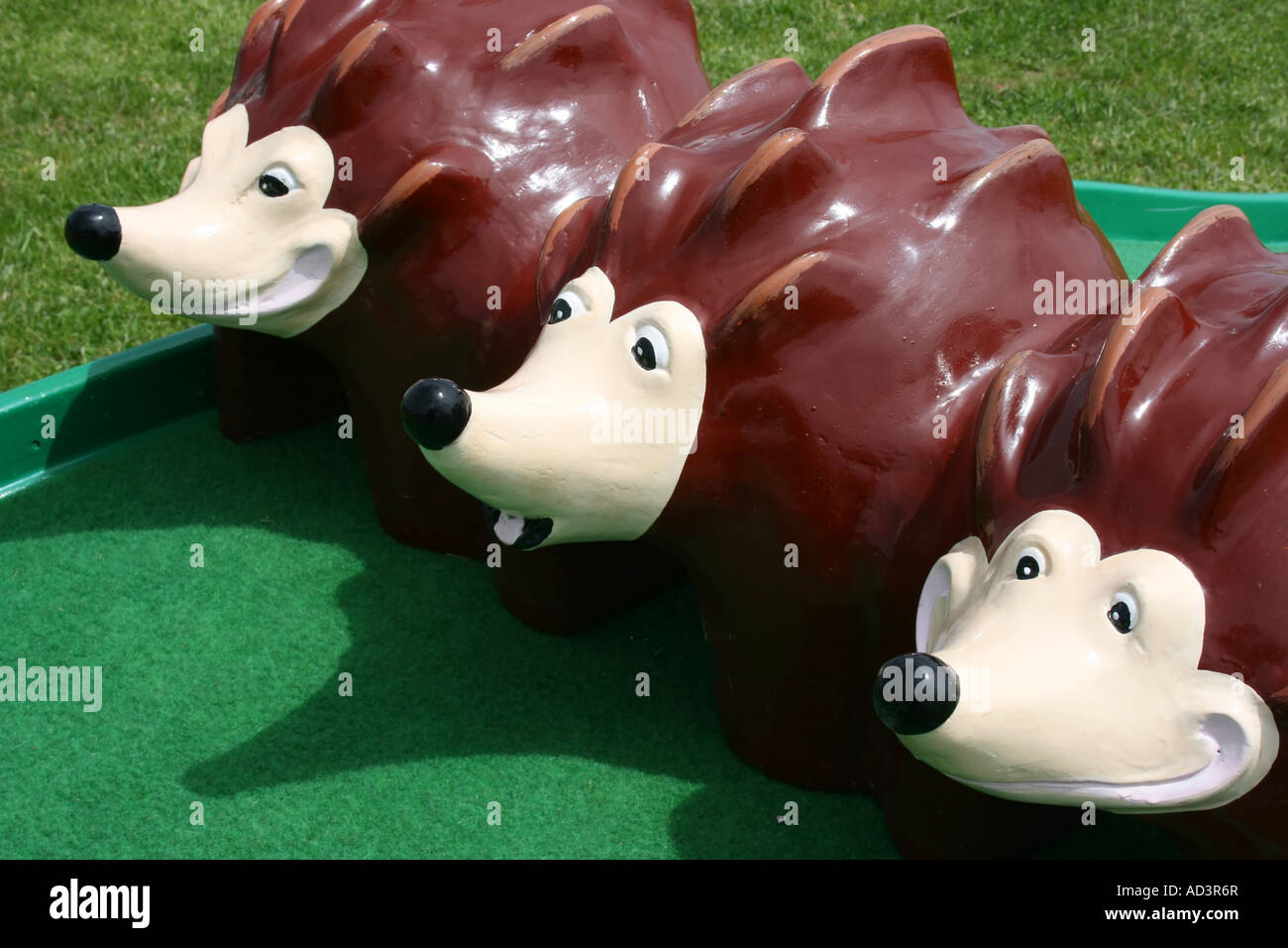 Model of three cute hedgehogs on crazy golf course at Pendine, Carmarthenshire, Wales - Stock Image