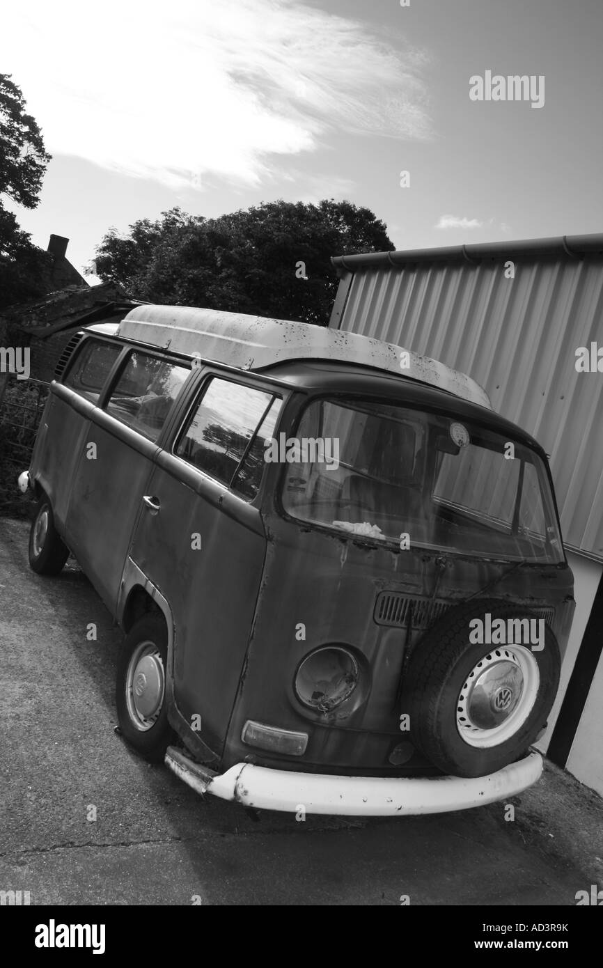 Beaten up old Volkswagen camper parked at old garage buildings, Pembrokeshire, South Wales - Stock Image