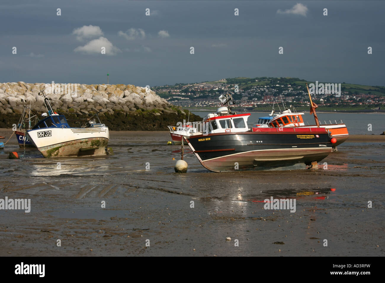 Small boats on beach at low tide at Rhos-on-Sea harbour, North Wales - Stock Image