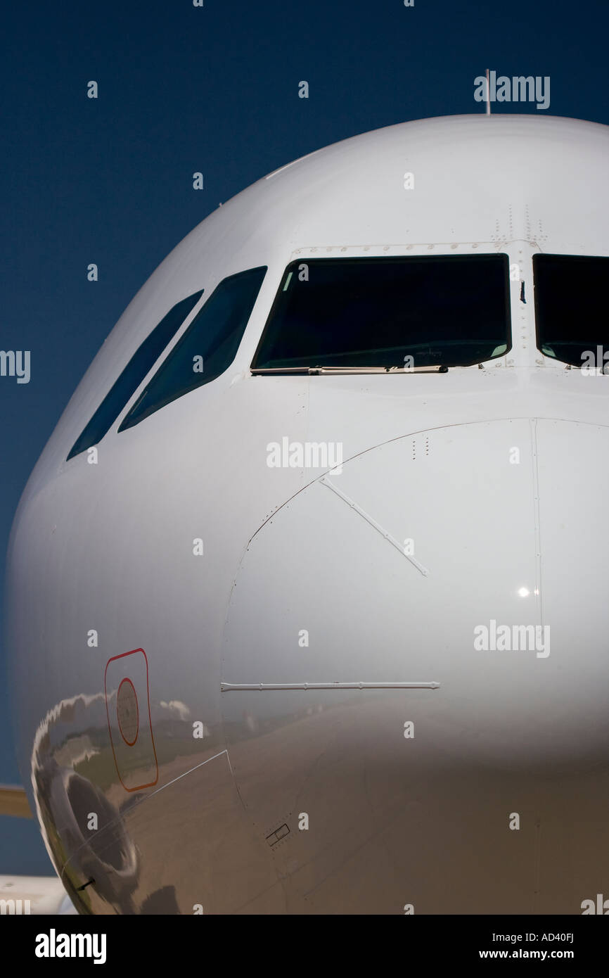 Frontal view of an Airbus A320. The starboard wing and engine nacelle are reflected in the white painted fuselage. - Stock Image