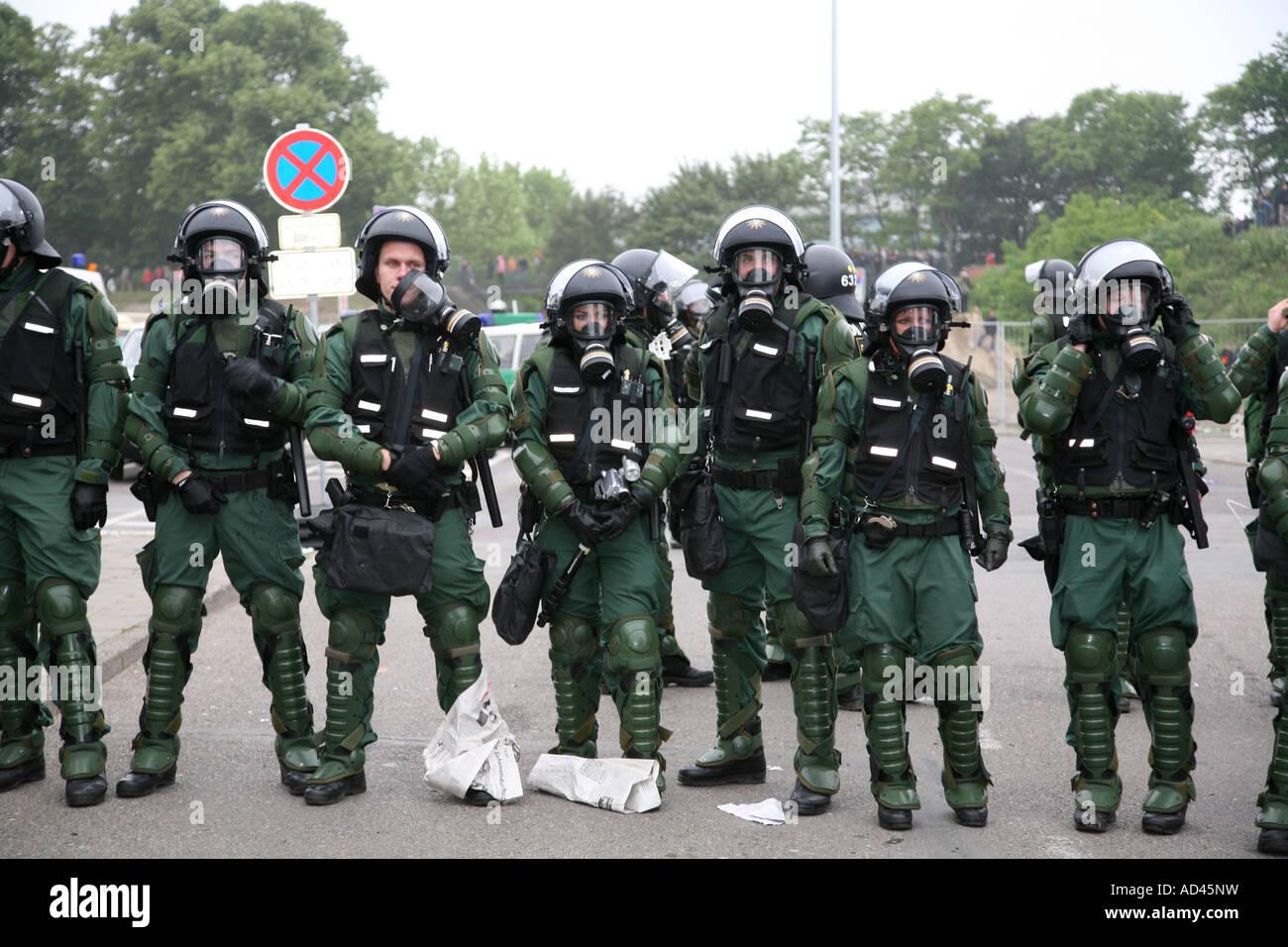 Policemen wearing gasmasks - Stock Image
