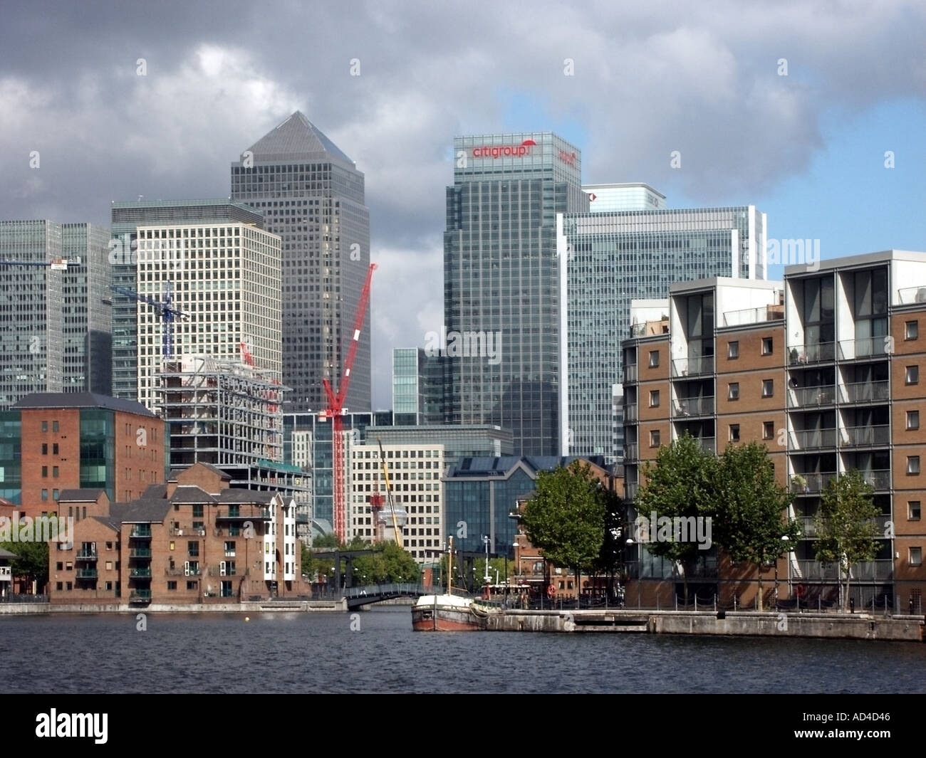 Docklands East London skyline including Canary Wharf tower and Citigroup building with Millwall outer dock waters - Stock Image
