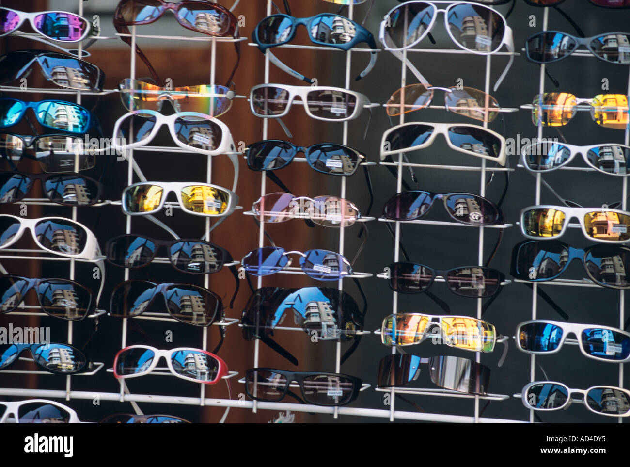Sunglasses on sale in a Spanish town with lady viewing from behind a rack - Stock Image