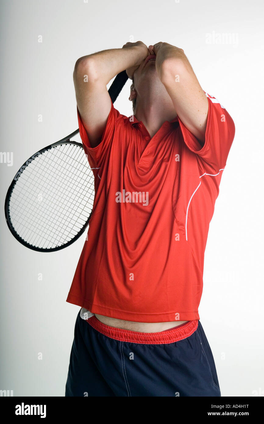 A tennis player covering his face in defeat - Stock Image