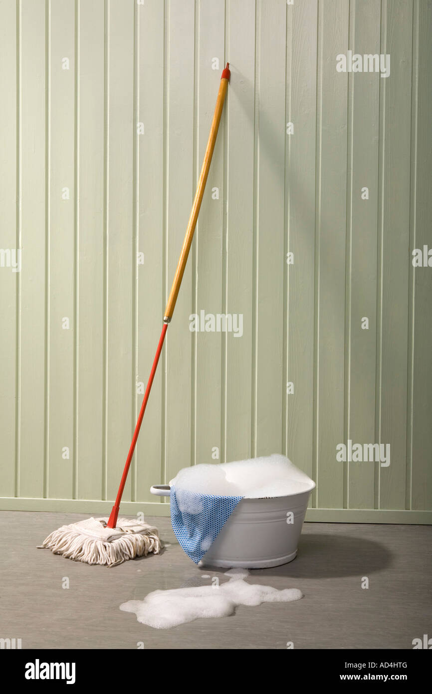 A bucket of soapy water and a mop - Stock Image