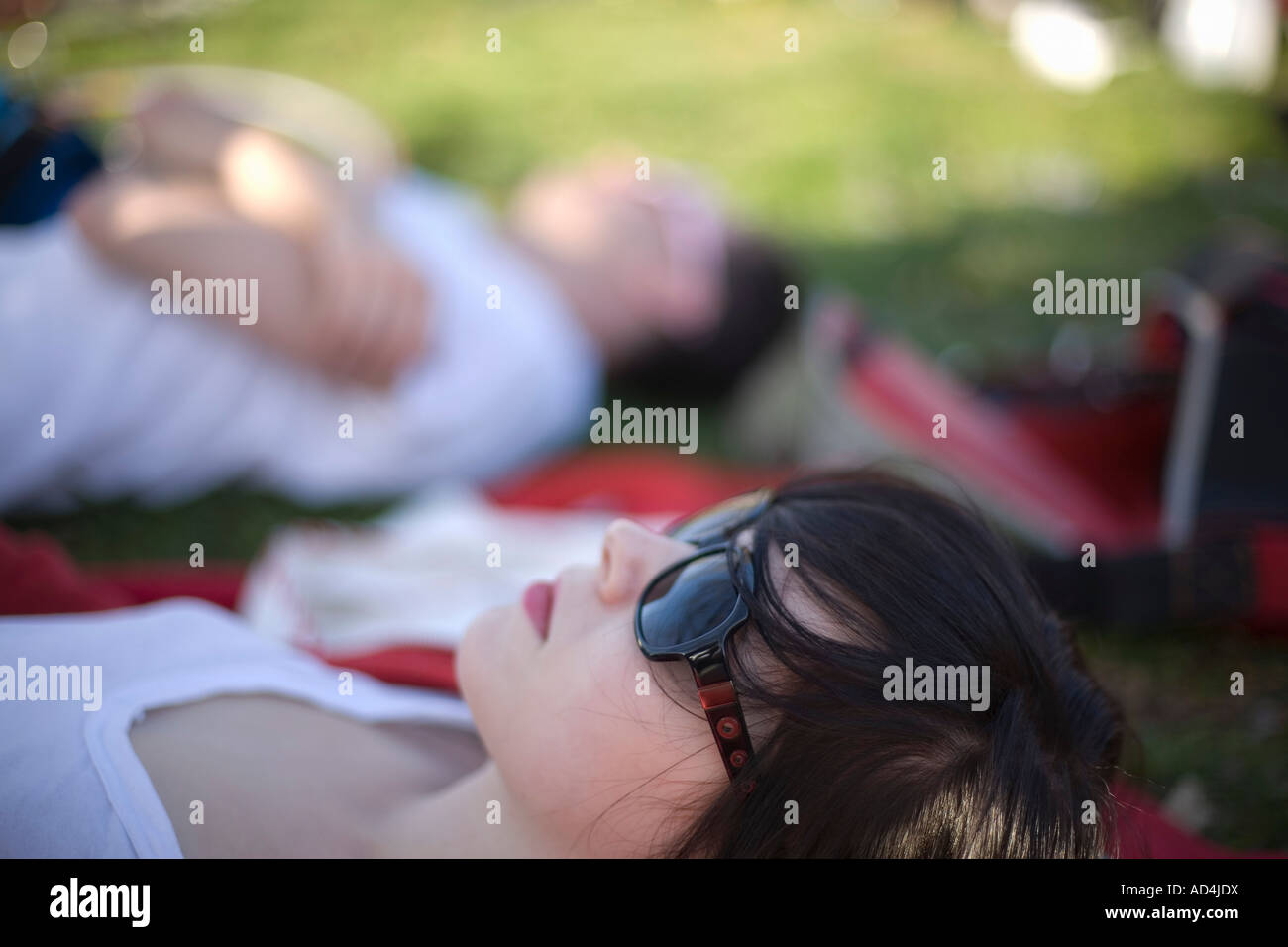 A young woman lying down in a park - Stock Image
