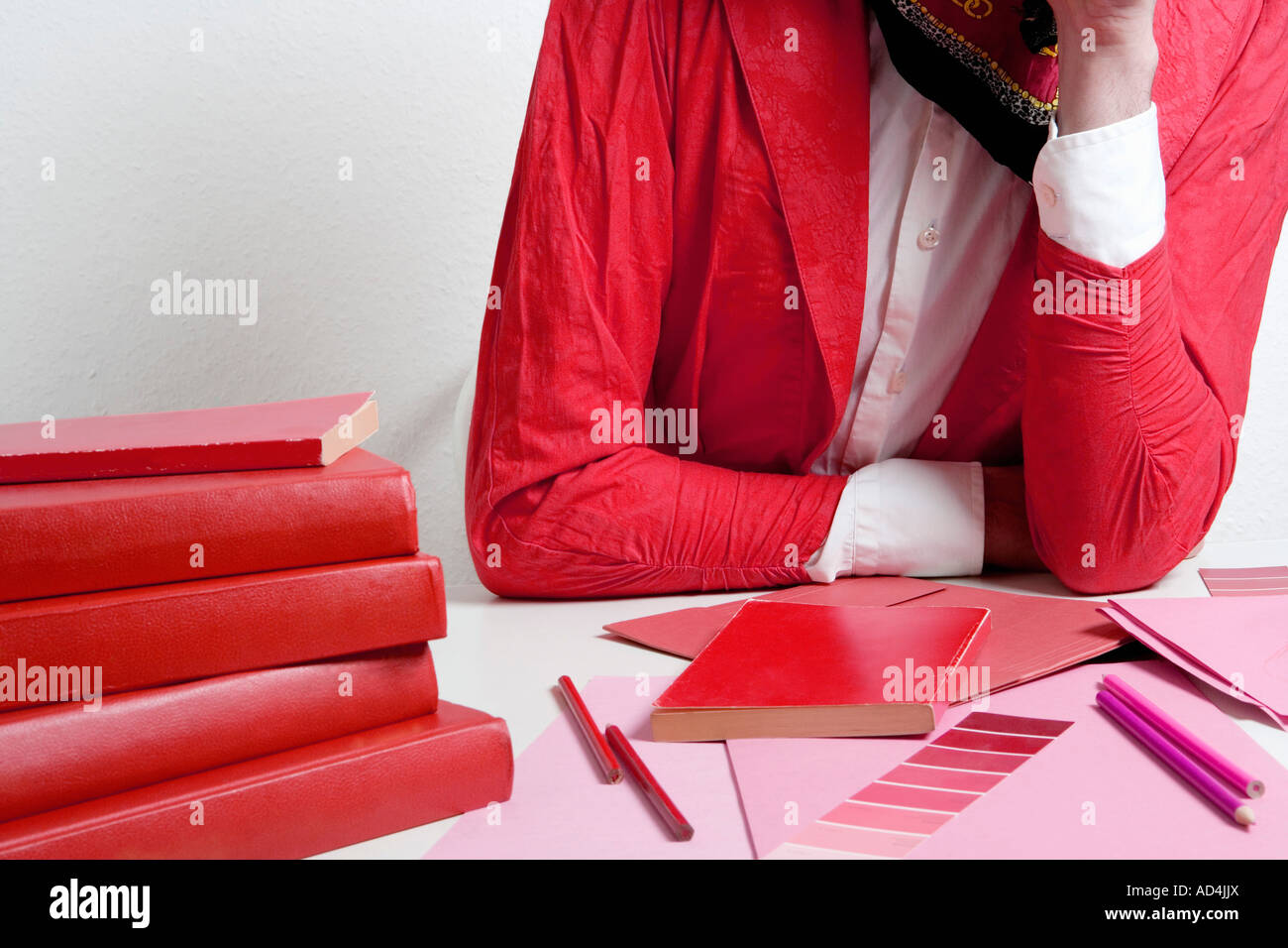 Woman leaning on a desk with design materials - Stock Image