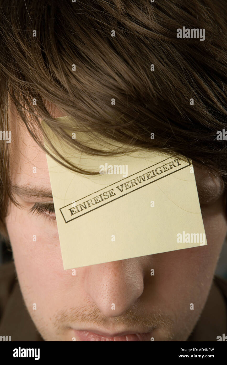 A man with an adhesive note on his forehead stamped 'Denied Entry' - Stock Image