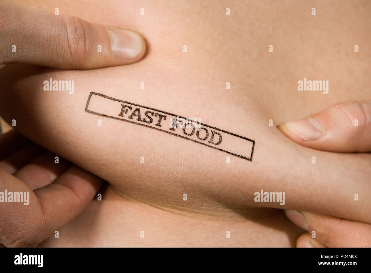 A man pinching part of his abdomen stamped 'Fast Food' - Stock Image
