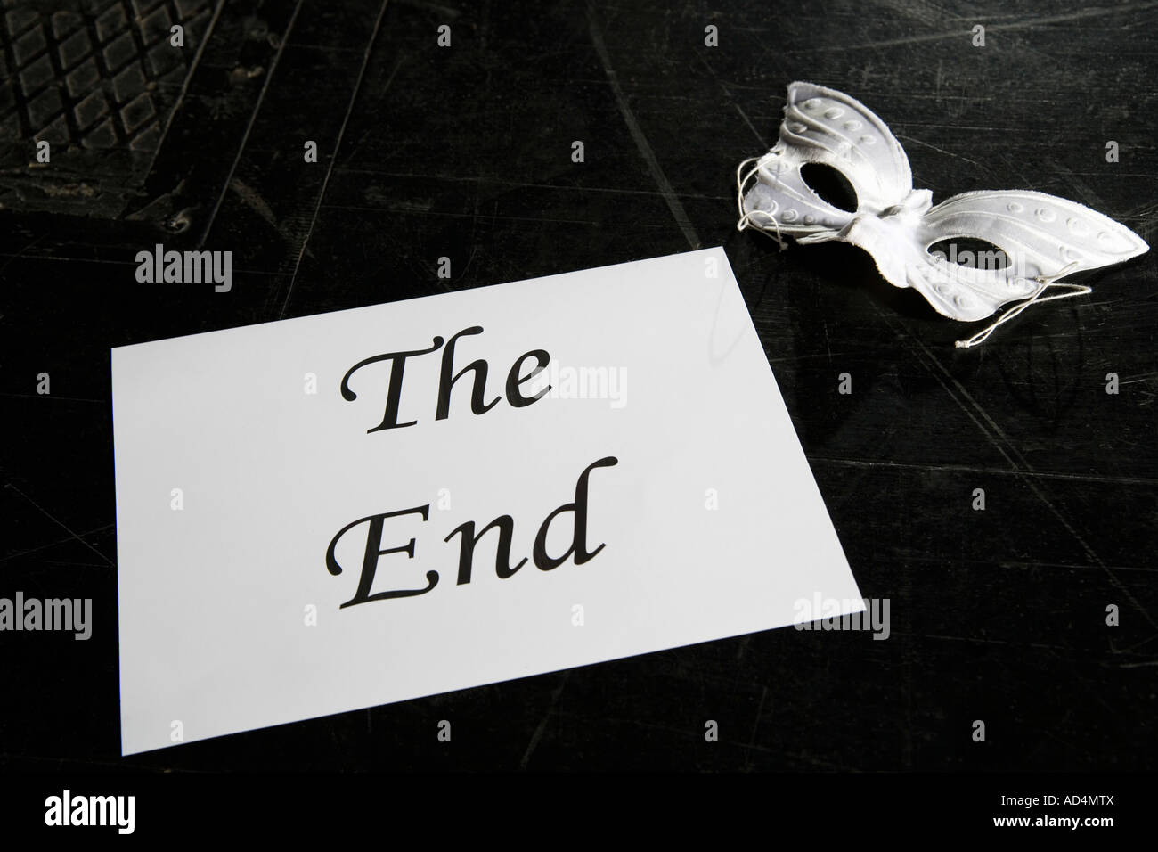 A mask and a sign for 'The End' on a theater stage - Stock Image