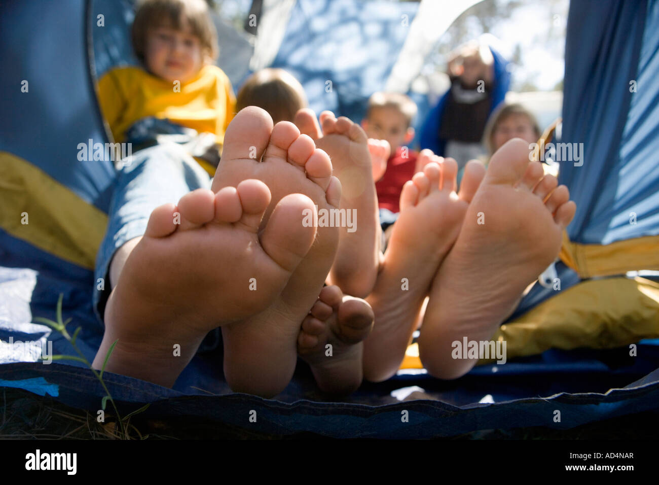 View of children's feet poking out of a tent - Stock Image