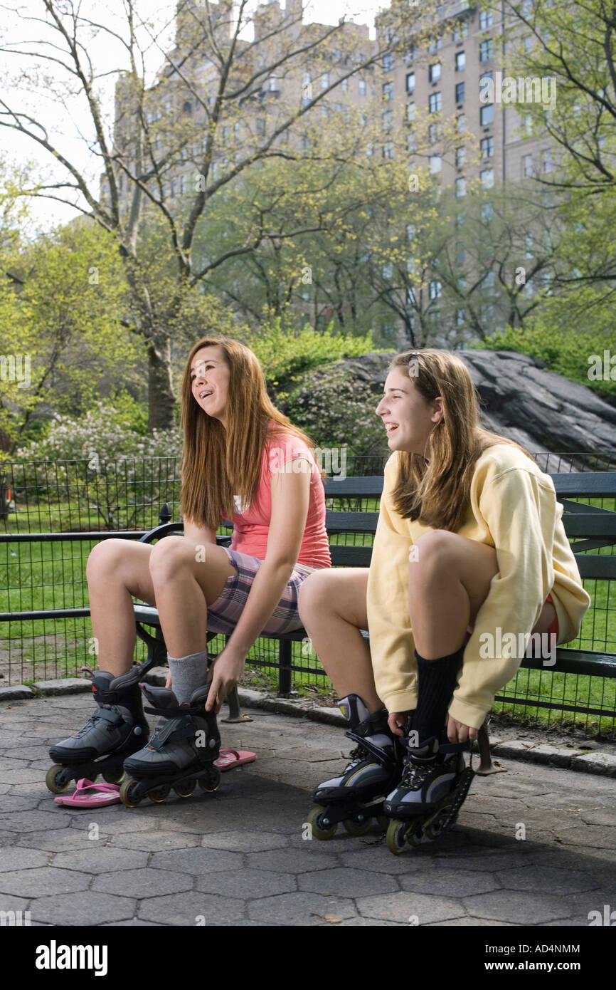 Two adolescent girls sitting on a park bench adjusting inline skates, Central Park, New York City Stock Photo